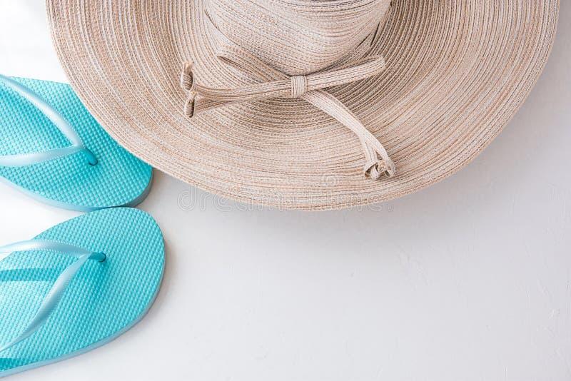 Κομψό καπέλο ήλιων γυναικών με τις μπλε παντόφλες παραλιών τόξων στην άσπρη χαλάρωση διακοπών παραλιών υποβάθρου στοκ φωτογραφία με δικαίωμα ελεύθερης χρήσης