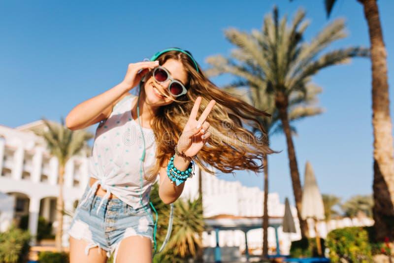 Κομψό κορίτσι με το όμορφο hairstyle στα γυαλιά ηλίου και τα σορτς τζιν που θέτουν πρόθυμα μπροστά από την οικοδόμηση και τους φο στοκ εικόνα