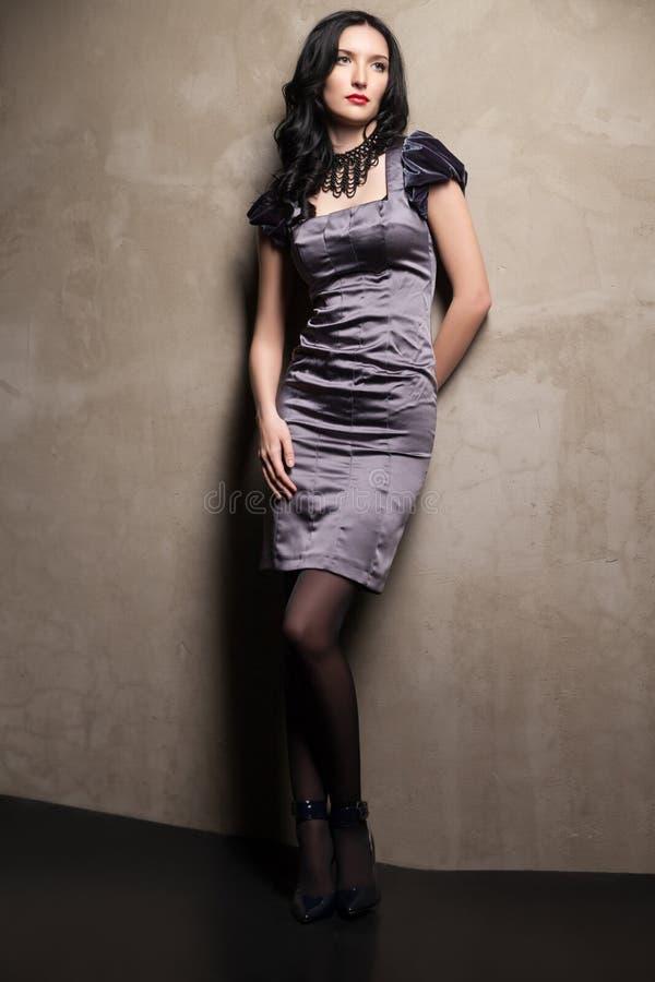 Κομψό κορίτσι στο γκρίζο φόρεμα στοκ εικόνες