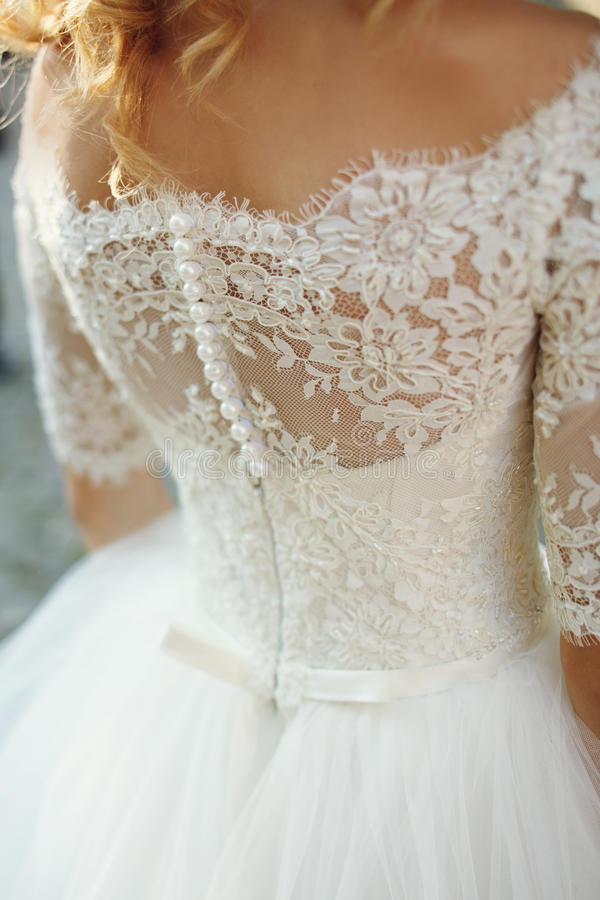 Κομψό μοντέρνο εκλεκτής ποιότητας άσπρο γαμήλιο φόρεμα με τις διακοσμήσεις πίσω στοκ εικόνες
