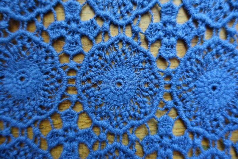 Κομψό μπλε δαντελλωτός ύφασμα στο ξύλο στοκ φωτογραφία