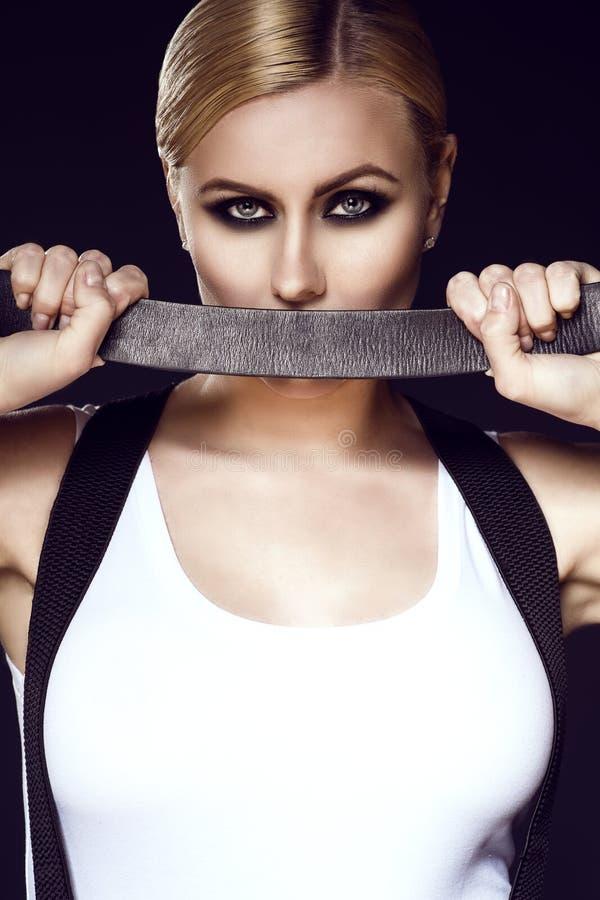 Κομψό ξανθό πρότυπο με την τργμένη πίσω τρίχα που φορά την άσπρη κορυφή με suspenders πέρα από τους ώμους της που καλύπτουν το στ στοκ εικόνα