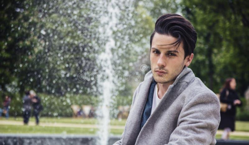 Κομψό παλτό μαλλιού νεαρών άνδρων υπαίθριο φορώντας στοκ εικόνες