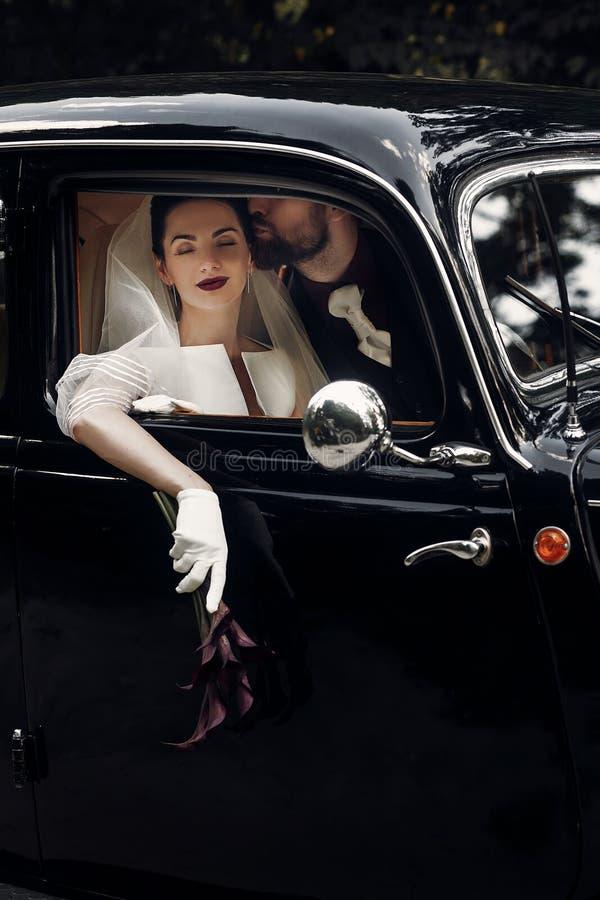 Κομψό φίλημα γαμήλιων ζευγών πολυτέλειας στο μοντέρνο μαύρο αυτοκίνητο Gorg στοκ φωτογραφία με δικαίωμα ελεύθερης χρήσης