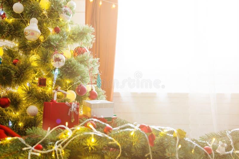 Κομψό χριστουγεννιάτικο δέντρο με τις διακοσμήσεις και τα δώρα στο κομψό πάτωμα σκληρού ξύλου πέρα από το παράθυρο στοκ εικόνες
