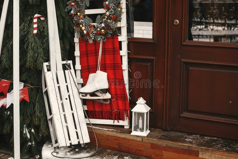 Κομψό χριστουγεννιάτικο στεφάνι, λευκό ξύλινο έλκηθρο και παγοπέδιλο μπροστά από το κατάστημα στο κέντρο της πόλης Οδός των Χριστ στοκ φωτογραφία με δικαίωμα ελεύθερης χρήσης