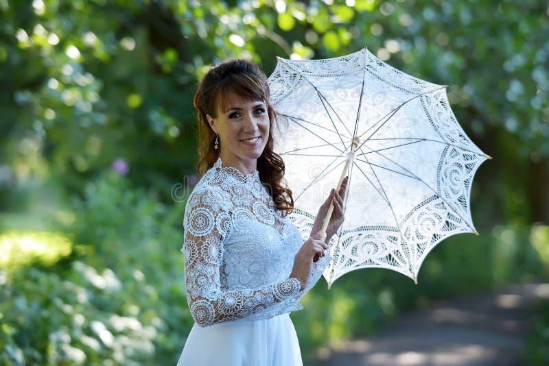Κομψό brunette σε ένα εκλεκτής ποιότητας άσπρο φόρεμα στοκ εικόνες