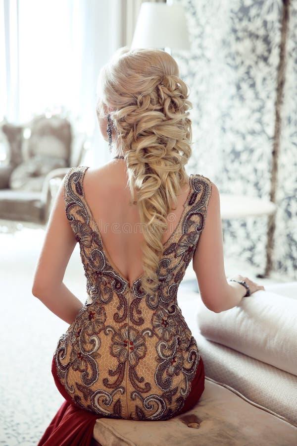 κομψό hairstyle Όμορφη ξανθή γυναίκα στο κόκκινο Si φορεμάτων μόδας στοκ φωτογραφία