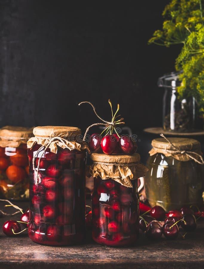 Κονσέρβα συγκομιδών Τα βάζα γυαλιού με compote κερασιών στο σκοτεινό αγροτικό πίνακα κουζινών με άλλη κονσέρβα για για το χειμώνα στοκ εικόνες