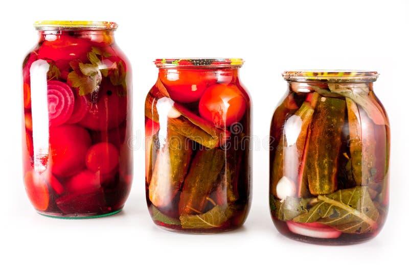 Κονσερβοποιημένα ντομάτες και αγγούρια σε ένα βάζο γυαλιού σε ένα άσπρο υπόβαθρο στοκ εικόνες