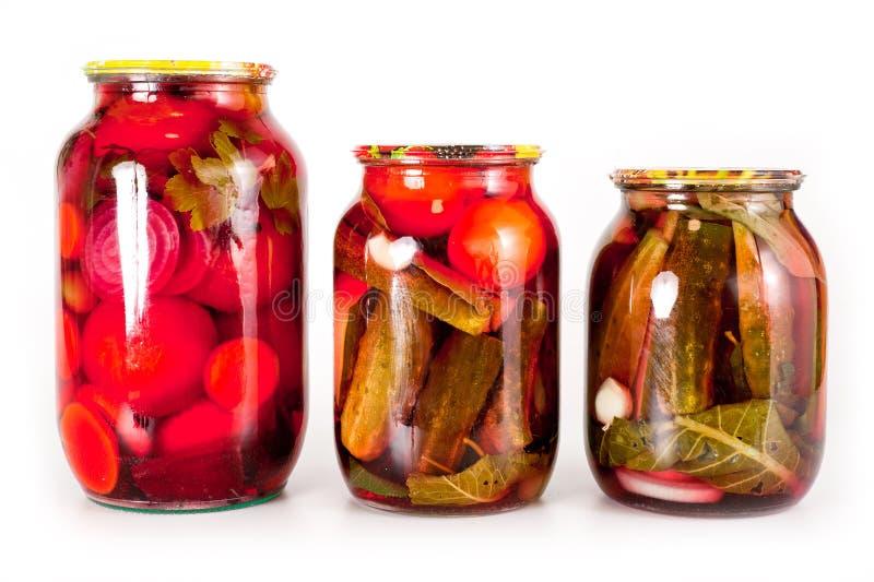 Κονσερβοποιημένα ντομάτες και αγγούρια σε ένα βάζο γυαλιού σε ένα άσπρο υπόβαθρο στοκ εικόνα