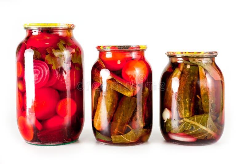 Κονσερβοποιημένα ντομάτες και αγγούρια σε ένα βάζο γυαλιού σε ένα άσπρο υπόβαθρο στοκ εικόνα με δικαίωμα ελεύθερης χρήσης