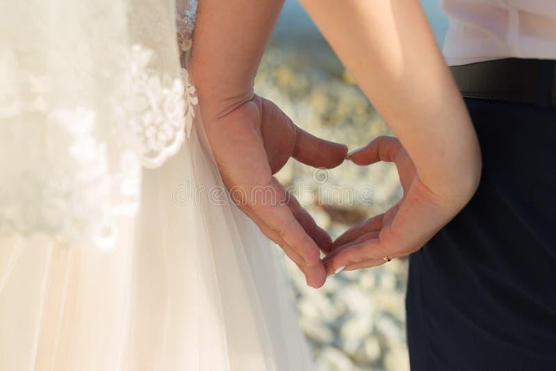 Κοντινό πλάνο ενός ζευγαριού αγάπης που κρατά ή κάνει χέρι για την καρδιά, ως ρομαντική ιδέα γάμου στοκ φωτογραφία