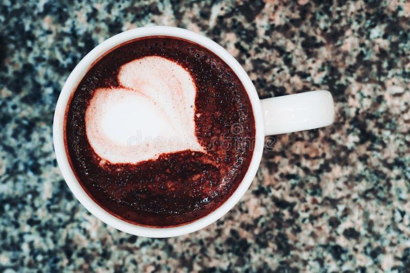 Κοντινό πλάνο ζεστής σοκολάτας και κύπελλο με καρδιακές καλλιτεχνικές φιγούρες στην κορυφή του μαρμάρινου τραπεζιού στοκ φωτογραφία με δικαίωμα ελεύθερης χρήσης