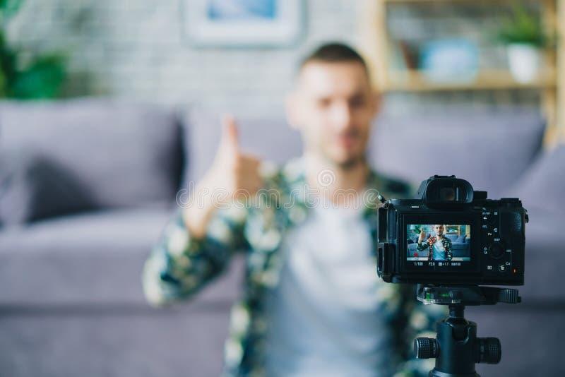 Κοντινό πλάνο κάμερας που μαγνητοσκοπεί μοντέρνο blogger που δείχνει βίντεο με μικρογραφίες στοκ εικόνα