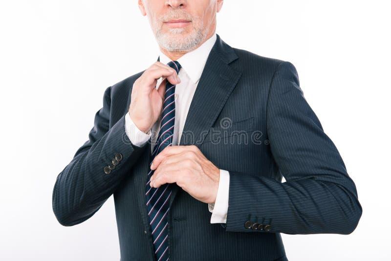 Κοντινό πορτρέτο ενός γέρου επιχειρηματία που διορθώνει τη γραβάτα του στοκ εικόνα με δικαίωμα ελεύθερης χρήσης