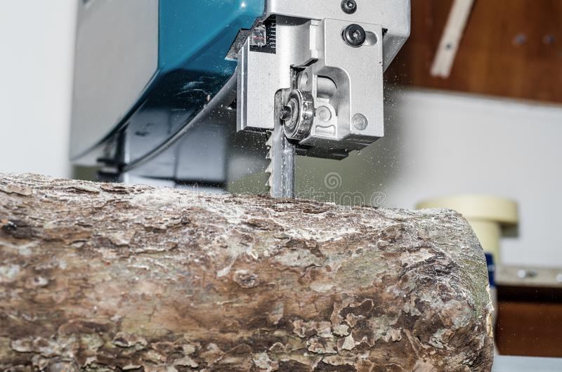 Κοπή ενός κούτσουρου στους πίνακες που χρησιμοποιούν ένα πριόνι ζωνών joinery Ξύλινες τέχνες ακατέργαστου ξύλου Εργασία στο εργοσ στοκ εικόνα