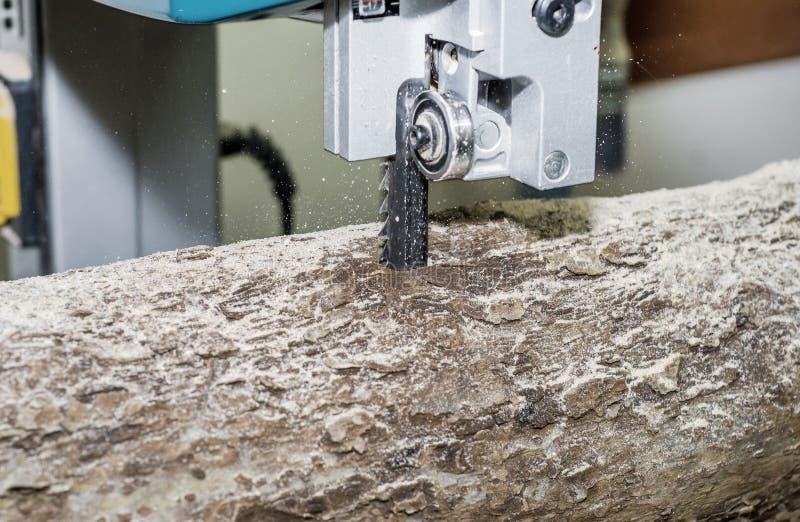 Κοπή ενός κούτσουρου στους πίνακες που χρησιμοποιούν ένα πριόνι ζωνών joinery Ξύλινες τέχνες ακατέργαστου ξύλου Εργασία στο εργοσ στοκ εικόνες