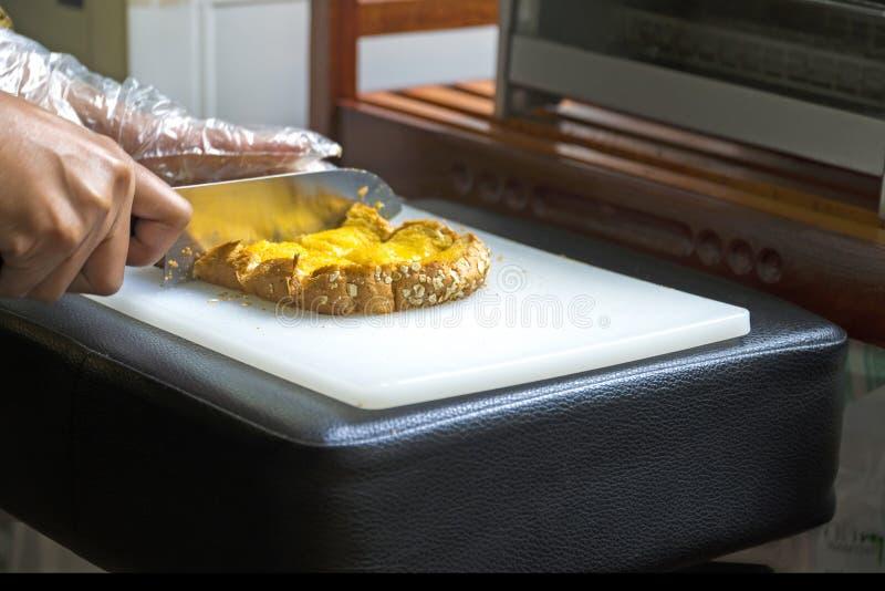 Κοπή μαχαιριών χεριών του τεμαχισμένου αρτοποιείου ψωμιού στοκ φωτογραφία
