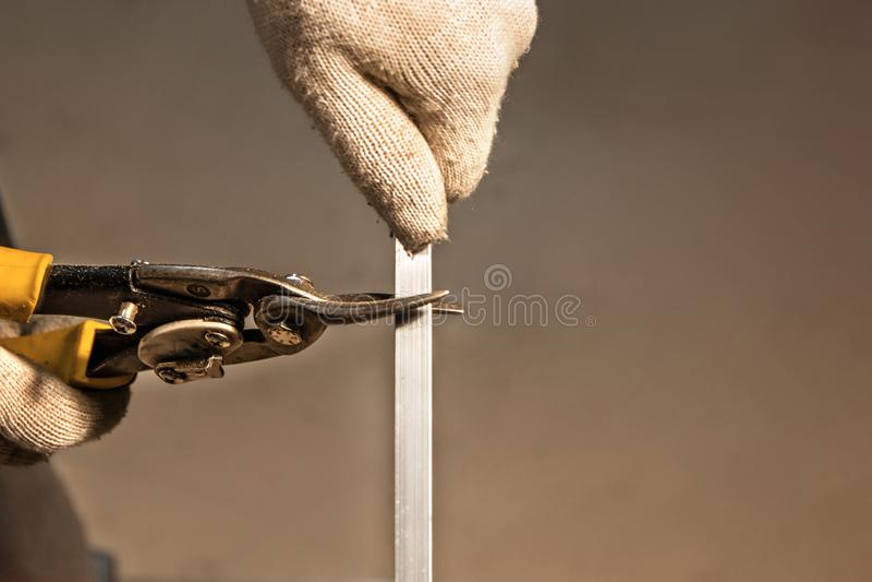 Κοπή της ράγας μετάλλων με το ισχυρό βιομηχανικό χειροποίητο ψαλίδι με τα χέρια στοκ φωτογραφία