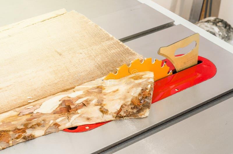 Κοπή του πίνακα σε ένα κυκλικό πριόνι σε ένα εργαστήριο ξυλουργικής στοκ εικόνες