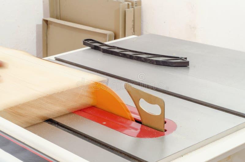 Κοπή του πίνακα σε ένα κυκλικό πριόνι σε ένα εργαστήριο ξυλουργικής στοκ εικόνα με δικαίωμα ελεύθερης χρήσης