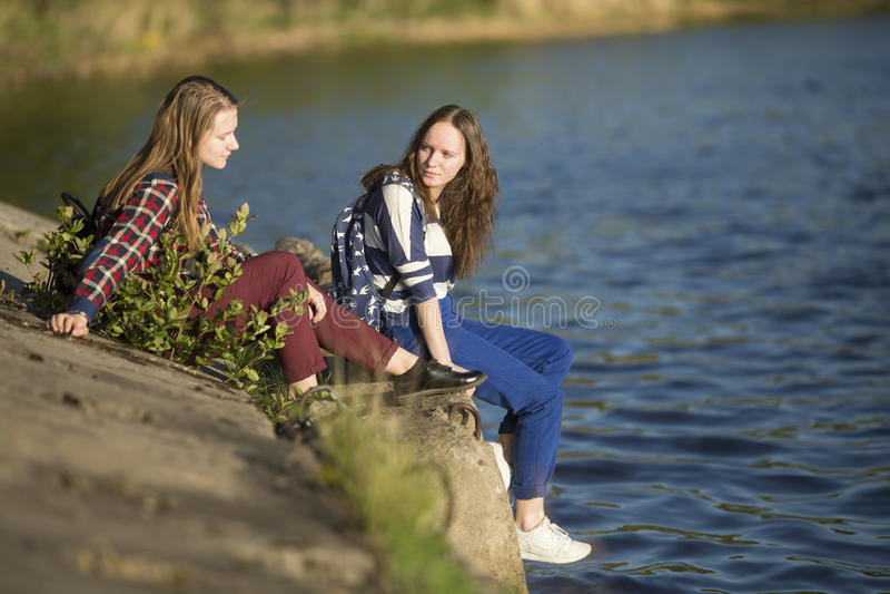 Κορίτσια εφήβων που κάθονται σε μια αποβάθρα κοντά στο νερό Φύση στοκ εικόνες με δικαίωμα ελεύθερης χρήσης