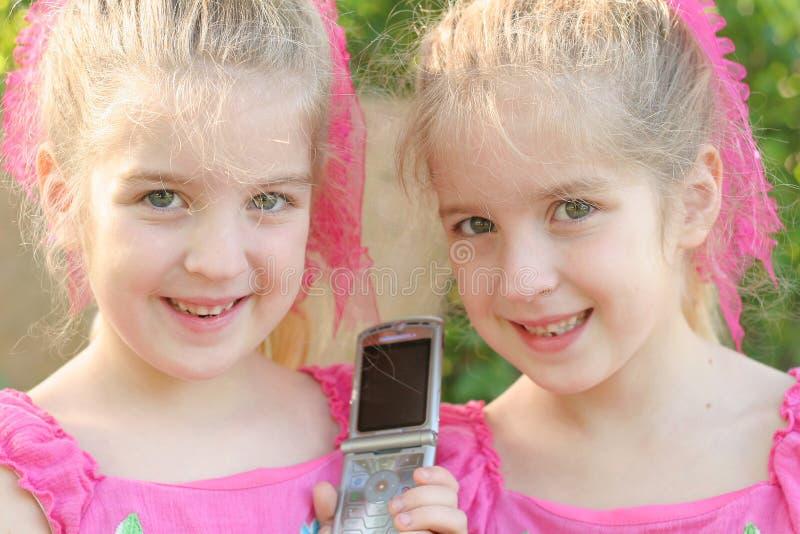 κορίτσια κυττάρων phon που μοιράζονται το δίδυμο στοκ εικόνες