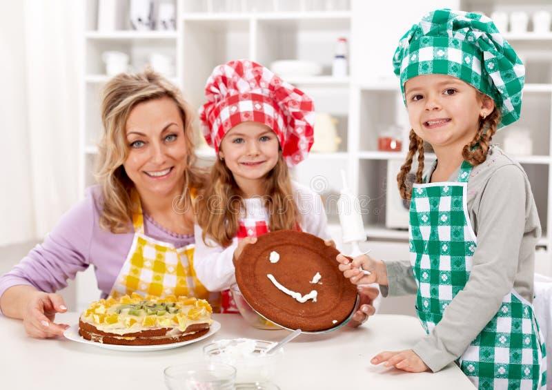 Κορίτσια λίγων αρχιμαγείρων με τη μητέρα τους που κατασκευάζει ένα κέικ στοκ εικόνα με δικαίωμα ελεύθερης χρήσης