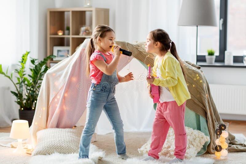 Κορίτσια με την κιθάρα και το μικρόφωνο που παίζουν στο σπίτι στοκ εικόνα