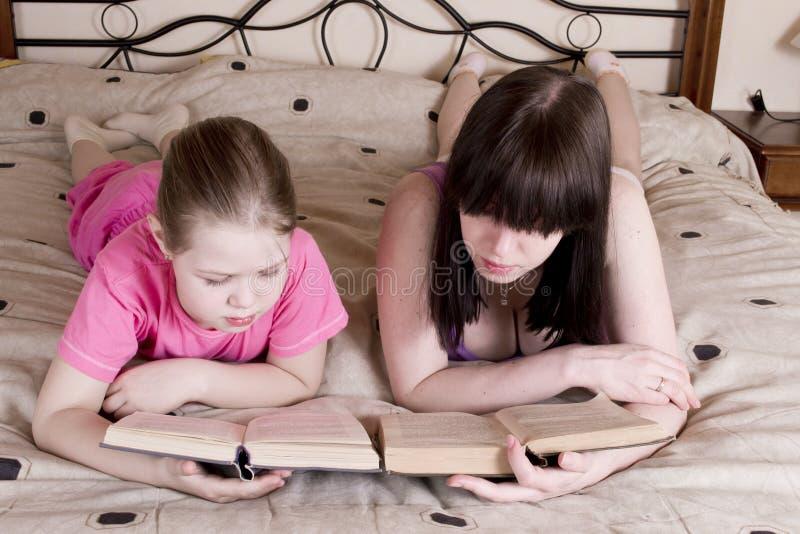 Κορίτσια που διαβάζουν το βιβλίο στο κρεβάτι στοκ φωτογραφία