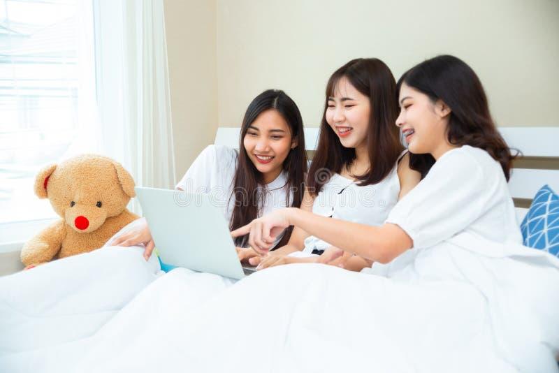 Κορίτσια που κοιτούν χαρούμενες ταινίες σε φορητό υπολογιστή μαζί στην κρεβατοκάμαρα στοκ εικόνα με δικαίωμα ελεύθερης χρήσης