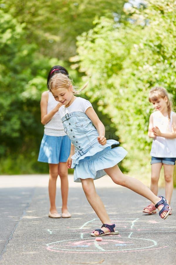Κορίτσια που παίζουν hopscotch για την καλή κατάρτιση δεξιοτήτων στοκ εικόνα