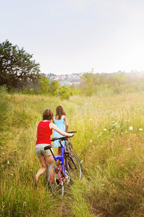 Κορίτσια που περπατούν τα ποδήλατα στον τομέα στοκ εικόνες