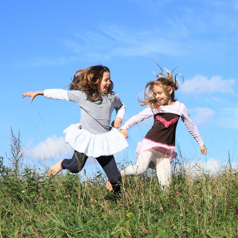 Κορίτσια που πηδούν στη χλόη στοκ φωτογραφία με δικαίωμα ελεύθερης χρήσης