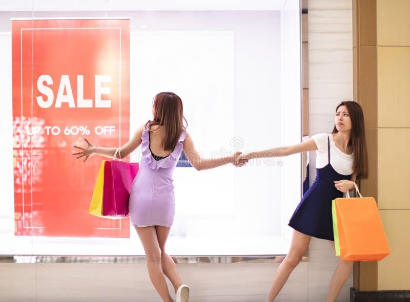 Κορίτσια που προσέχουν την αφίσα έκπτωσης και που ψωνίζουν στη λεωφόρο στοκ εικόνες