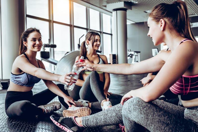 Κορίτσια που χαλαρώνουν μετά από το workout και το πόσιμο νερό στοκ εικόνα με δικαίωμα ελεύθερης χρήσης