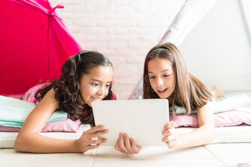 Κορίτσια που χρησιμοποιούν τις εφαρμογές στην ψηφιακή ταμπλέτα στις σκηνές στοκ εικόνα με δικαίωμα ελεύθερης χρήσης