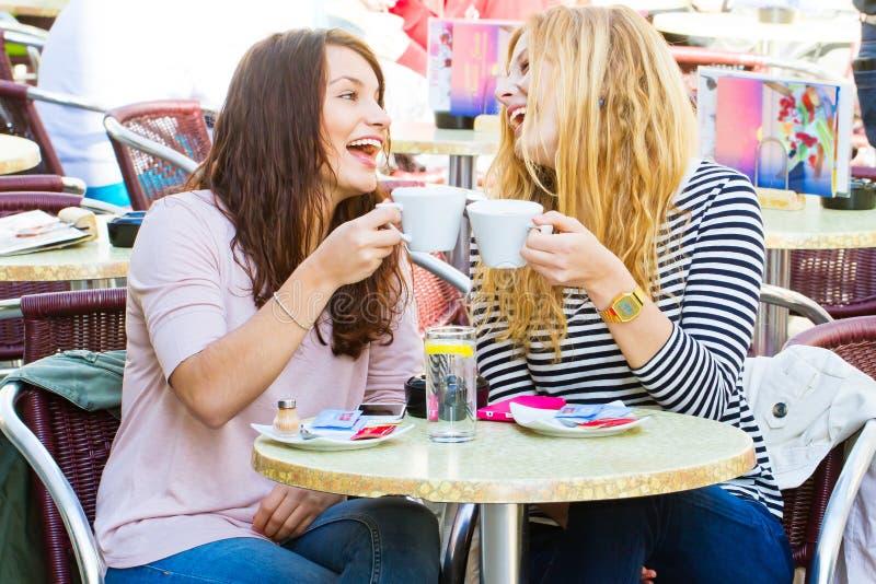 Κορίτσια σε έναν καφέ που έχει τη διασκέδαση στοκ εικόνες