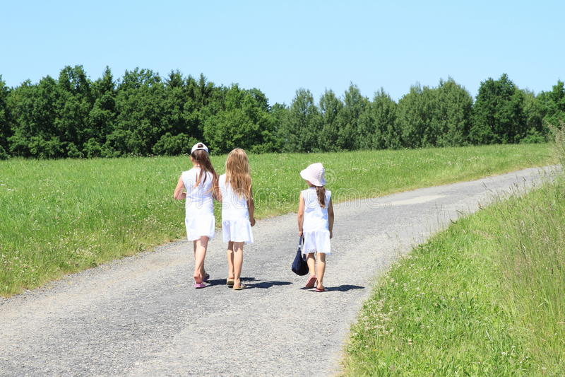 Κορίτσια στα άσπρα φορέματα στο δρόμο στοκ εικόνα