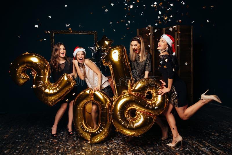 Κορίτσια στα καπέλα Santa που φέρνουν χρωματισμένους τους χρυσός αριθμούς στοκ εικόνες