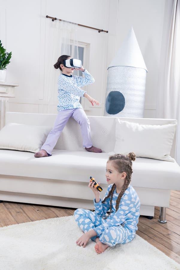 Κορίτσια στις πυτζάμες που παίζουν με την κάσκα και walkie-talkie εικονικής πραγματικότητας στοκ εικόνες με δικαίωμα ελεύθερης χρήσης