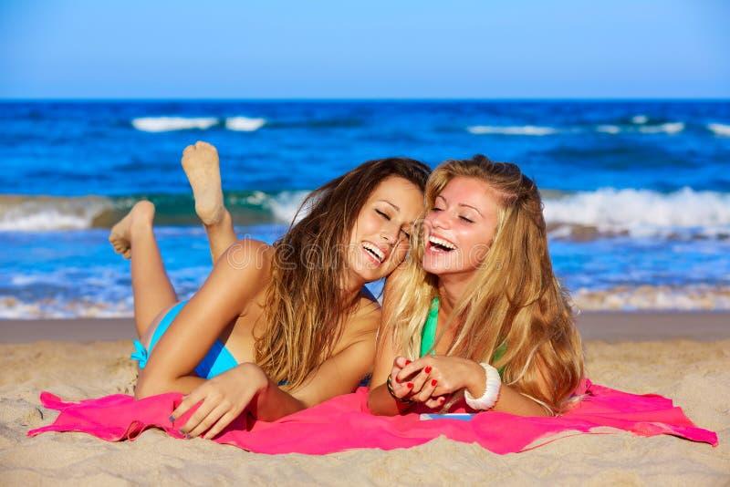 Κορίτσια φίλων που έχουν να βρεθεί γέλιου διασκέδασης την άμμο παραλιών στοκ εικόνα με δικαίωμα ελεύθερης χρήσης