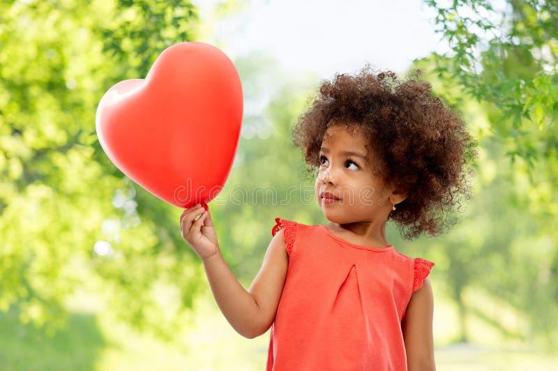 Κορίτσι αφροαμερικάνων με διαμορφωμένο το καρδιά μπαλόνι στοκ φωτογραφίες