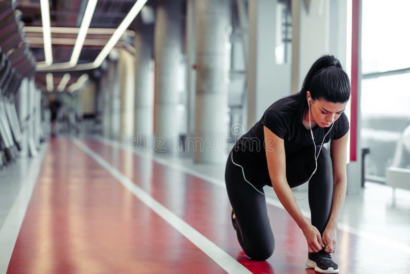 Κορίτσι για να κάνει κάτω τα κορδόνια στη γυμναστική ικανότητας πρίν τρέχει την άσκηση workout στοκ εικόνες