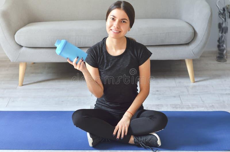 Κορίτσι γυμναστικής, σπίτι και διατροφή - χαμογελαστή έφηβη που κάθεται στο χαλί με αθλητικό εξοπλισμό στο σπίτι στοκ φωτογραφία με δικαίωμα ελεύθερης χρήσης