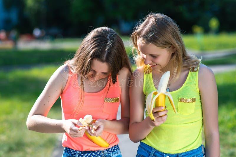 κορίτσι δύο φίλων Καλοκαίρι στη φύση Στα χέρια των μπανανών εκμετάλλευσης Οι χειρονομίες των χεριών καθαρίζουν την μπανάνα ενάντι στοκ φωτογραφίες με δικαίωμα ελεύθερης χρήσης