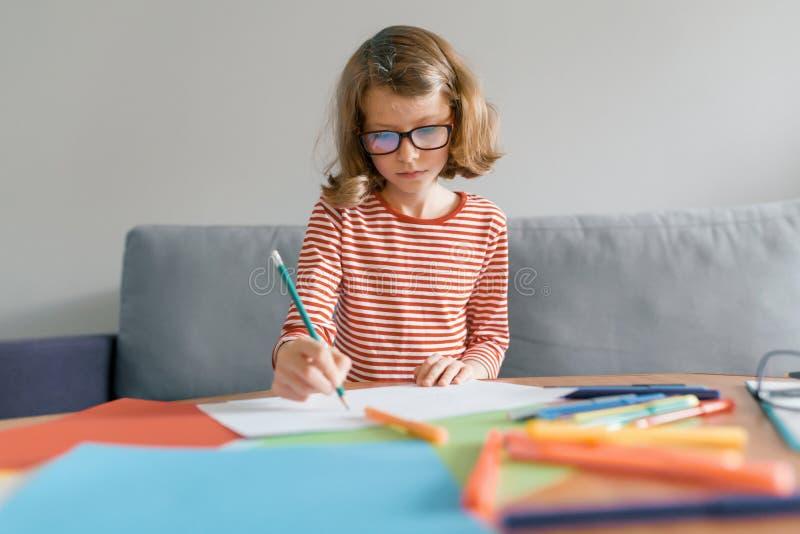Κορίτσι 8 ετών που κάθεται στον καναπέ που σύρει στο σπίτι το γράψιμο με το μολύβι στο σημειωματάριο Παιδί ξανθό με τα γυαλιά που στοκ εικόνες με δικαίωμα ελεύθερης χρήσης