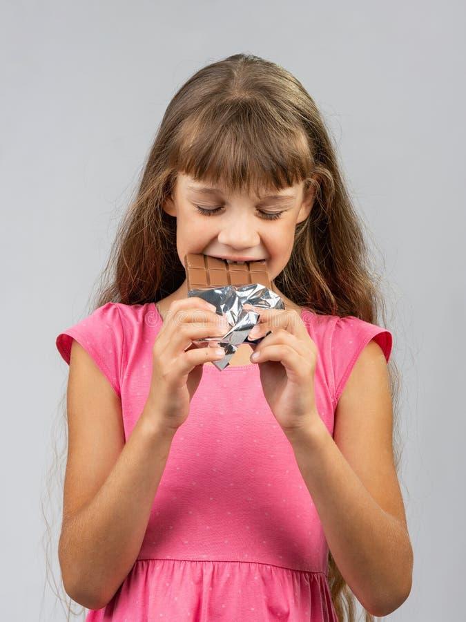 Κορίτσι εφήβων με τη σοκολάτα δαγκωμάτων ευχαρίστησης στοκ εικόνες