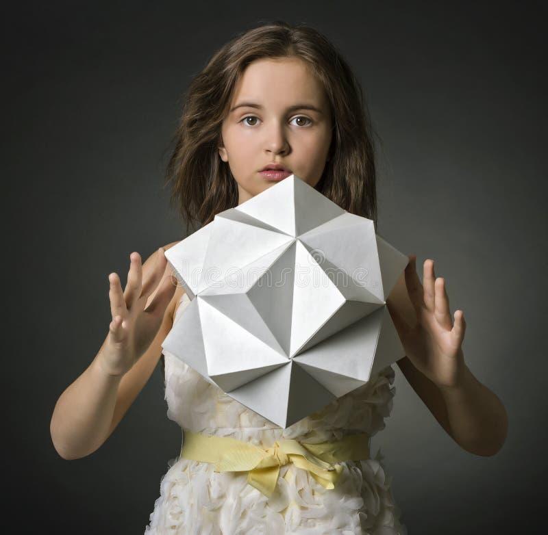 Κορίτσι εφήβων με το διαθέσιμο αριθμό πολυγώνων χεριών εγγράφου. στοκ εικόνες